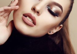 fashion studio photo of beautiful young woman with dark hair and evening makeup, wears fur coat